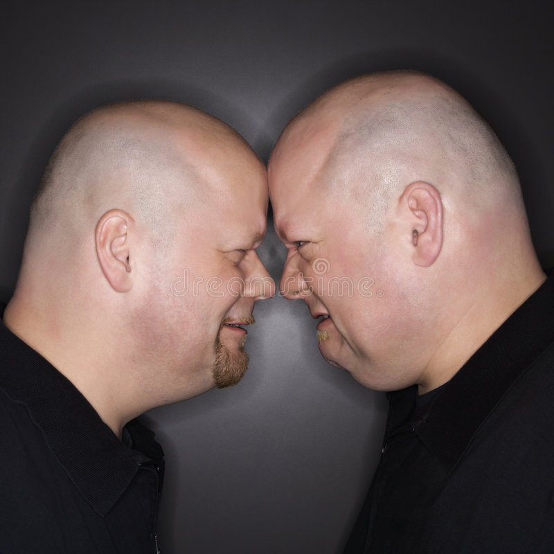 Twin men facing off. Caucasian bald mid adult identical twin men standing face to face with angry expression stock photo