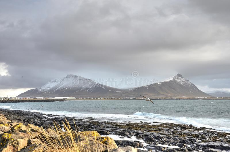 Twin peaks at Akranes, Iceland. View from the rocky beach at Akranes, Iceland towards two partially snow-covered mountains on the other side of the bay royalty free stock photo