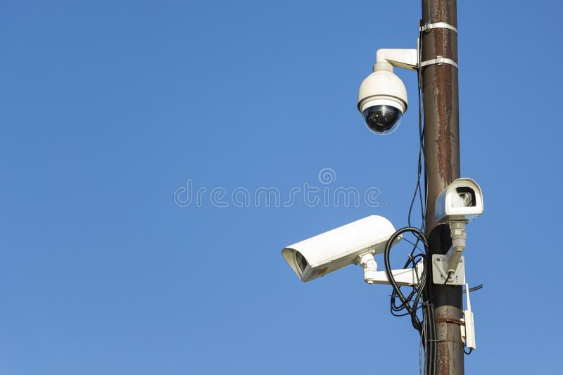 Twin security cameras on a pole against a blue sky. Twin security cameras on a pole against a blue sky royalty free stock photos