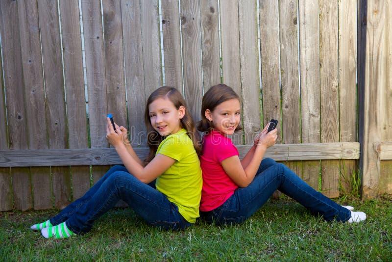 Download Twin Sister Girls Playing Smartphone Sitting On Backyard Lawn Stock Image - Image: 34090833