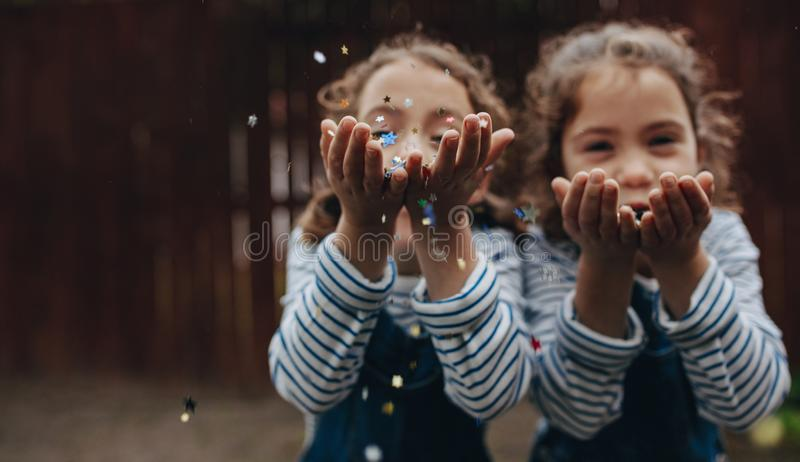Twin sisters enjoying blowing glitter royalty free stock photography