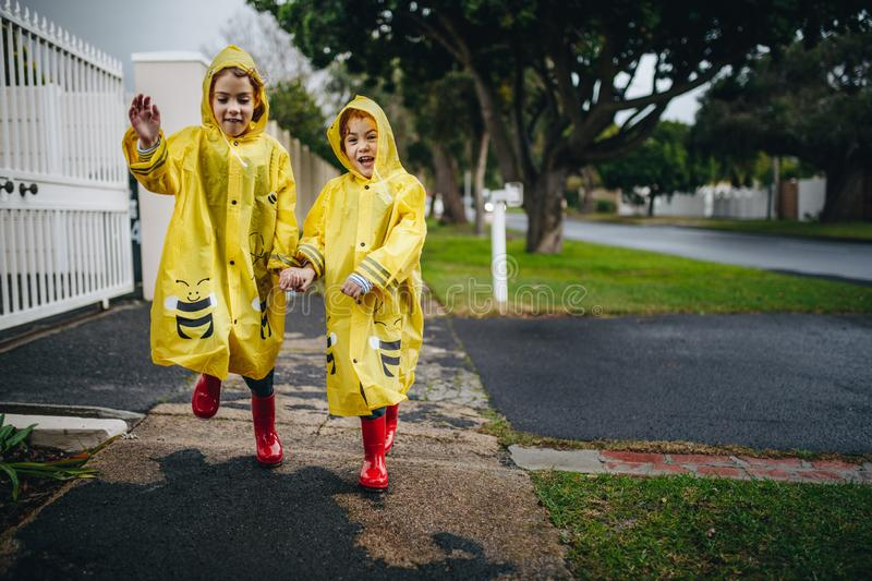 Twin sisters outdoors in raincoats stock image
