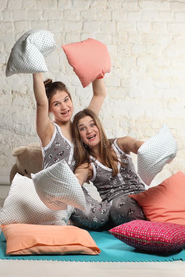 Twin sisters with pillows in the bedroom stock photos