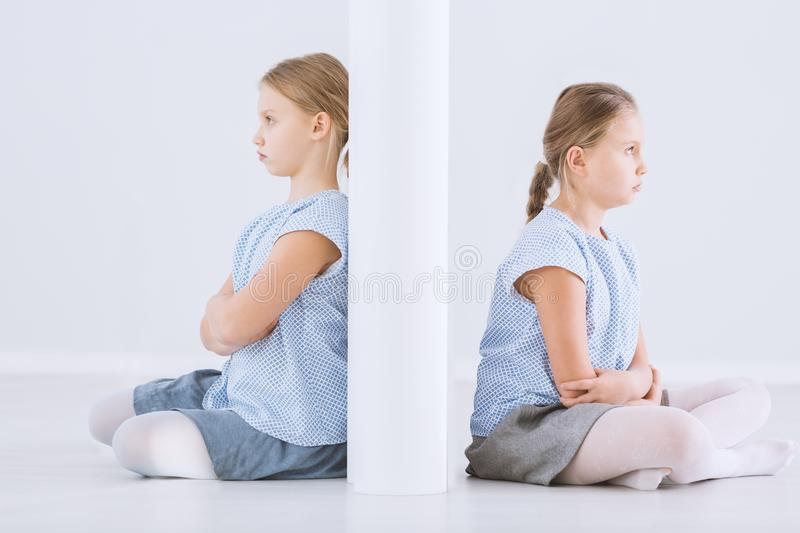 Twin sisters separated by wall stock photos