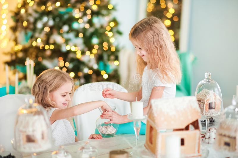 twin sisters at a table in the kitchen playing with a ginger house for the New Year. The kitchen in bright colors is decorated stock photography