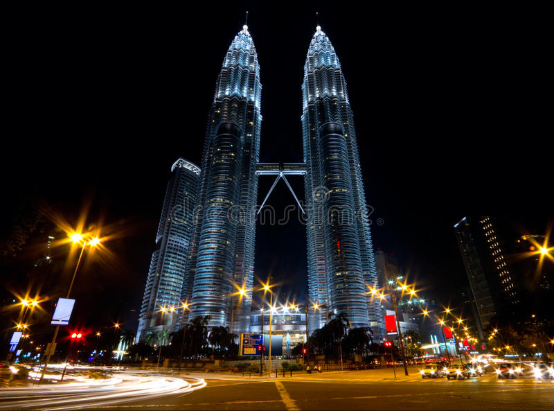 Twin skyscrapers and flowing traffic. Twin skyscrapers in the night with traffic flowing in front of them. Low angle view stock photography