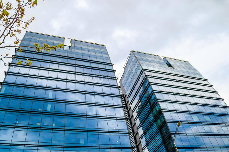 Twin skyscrapers with glass windows on a stormy day with clouds reflecting blue on the exterior of the buildings. royalty free stock photography