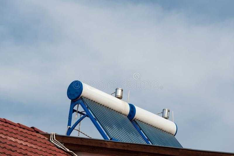 Twin solar water heater boilers on residentual house rooftop. On a cloudy day stock photography