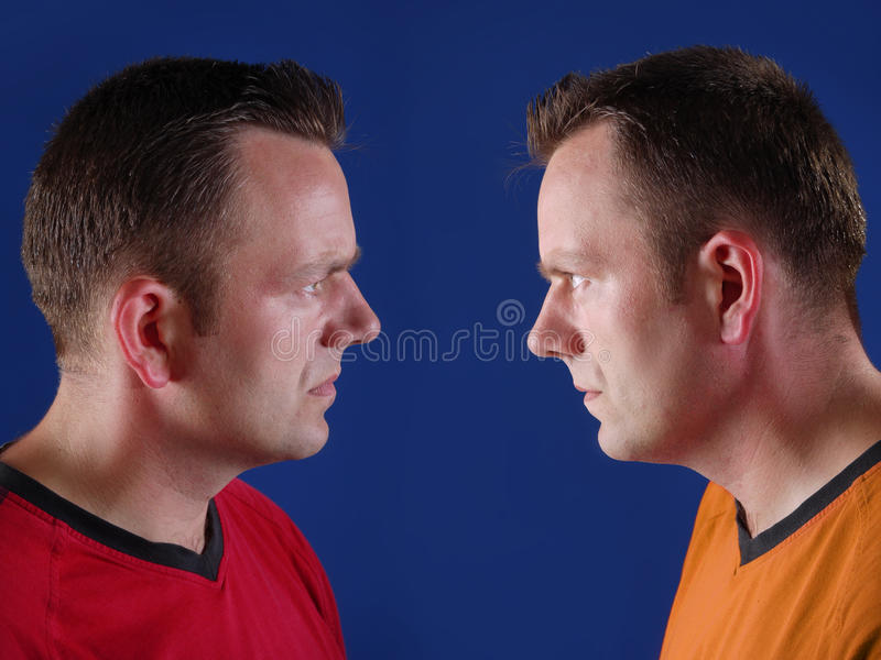 Twin sport supporters. Young twin brothers facing each other supporting opposite sports teams royalty free stock photos