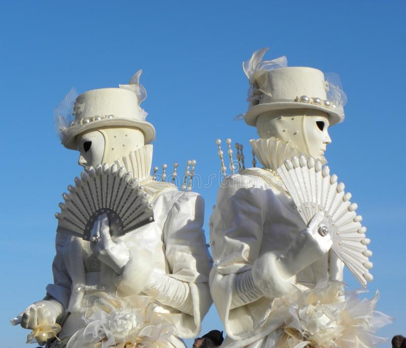 Twin white masks with fan, Carnival of Venice. Two identical white masks with fan looking in opposite directions, Carnival of Venice, Italy royalty free stock photos