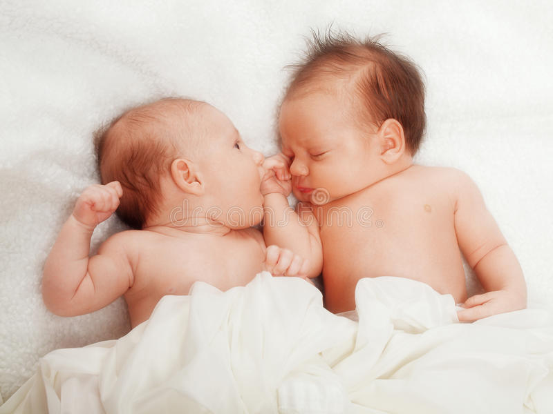 Twins. Newborn, one sleeping, in white royalty free stock photography