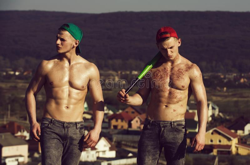Twins, athletic man with naked, torsos standing on mountain. Twins, athletic men or handsome athletes with naked, sexy, muscular torsos, six pack, ab, in red and royalty free stock images