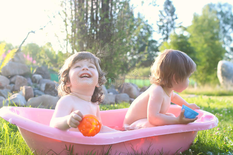 Twins boy and girl in bath water outdoor royalty free stock image