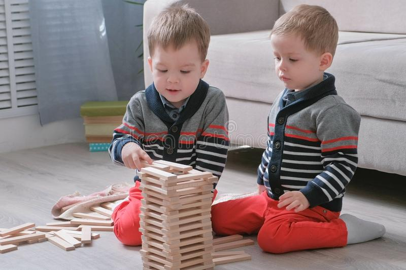Twins boys brothers are building from wooden blocks sitting on the floor by the sofa in their room. stock images