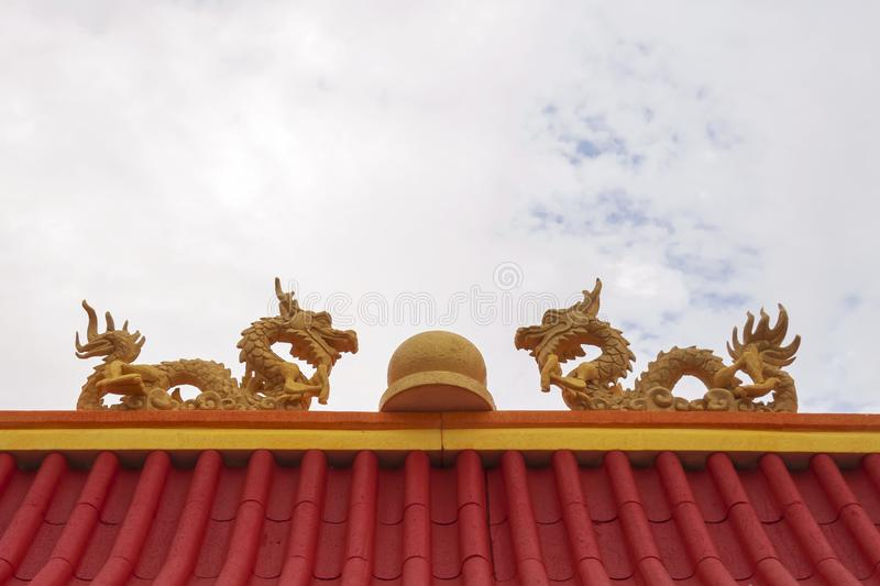 Twins foam crafting dragon with marble in the middle on top of red roof. stock images