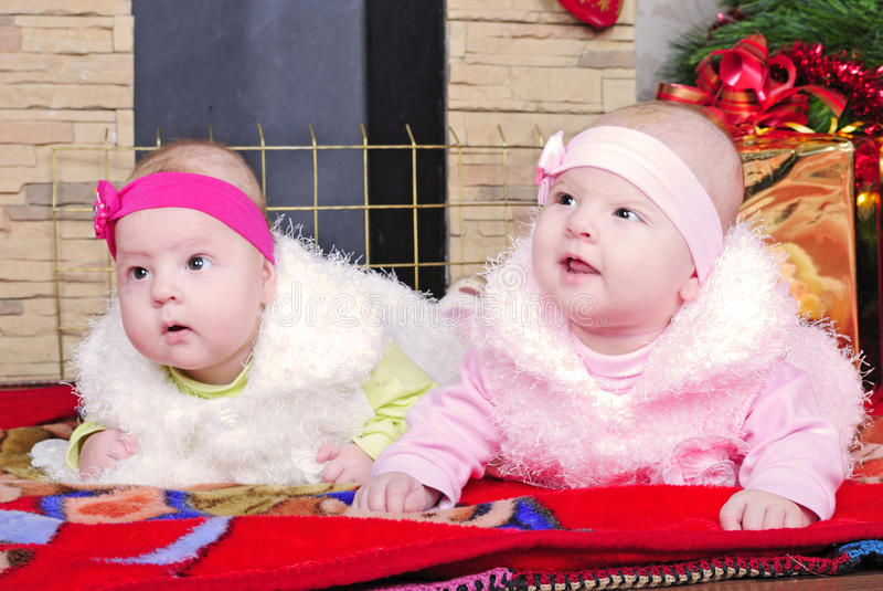 Twins girls near a Christmas tree royalty free stock image