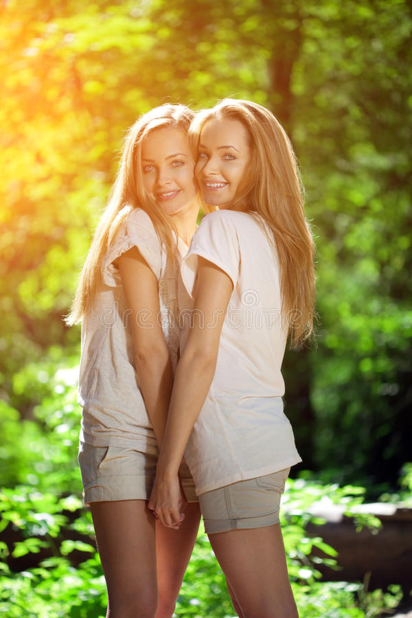 Twins. A group of young beautiful girls. Two women face close-up. Trendy stylish sisters royalty free stock photo