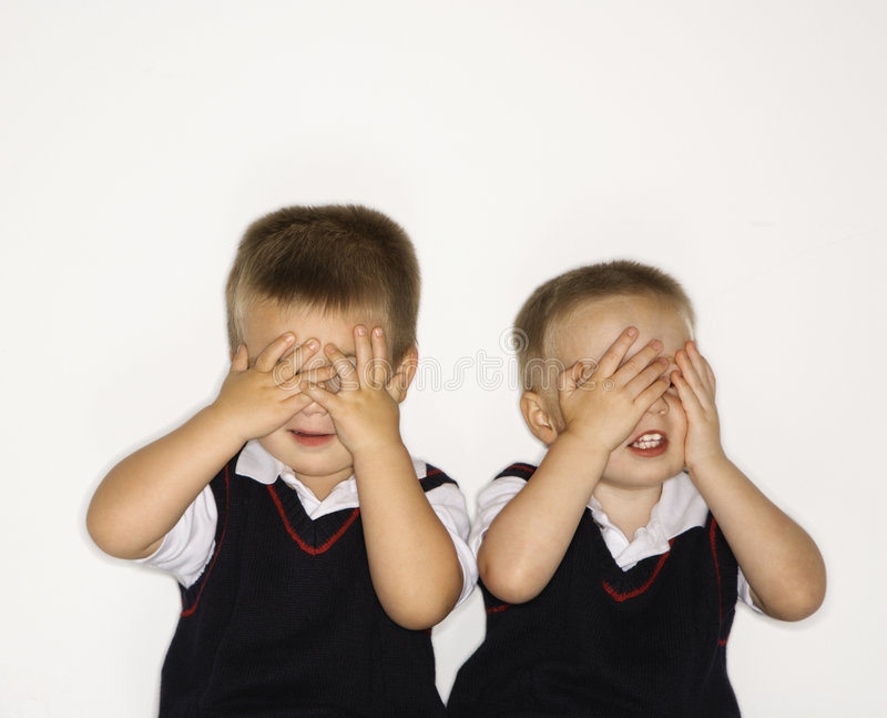 Twins with hands over eyes