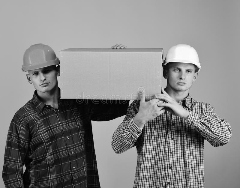 Twins with helmets move boxes. Delivery and moving concept. Men stand on pink background royalty free stock images