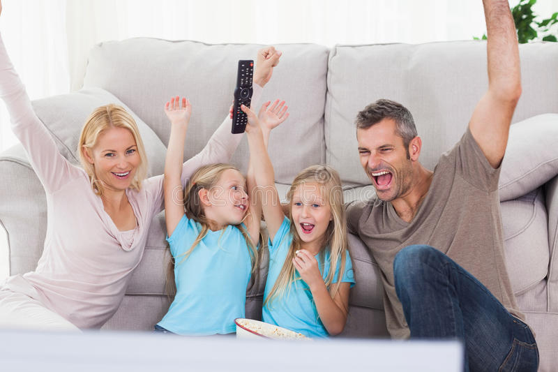 Twins And Parents Raising Arms While Watching Television Stock Images