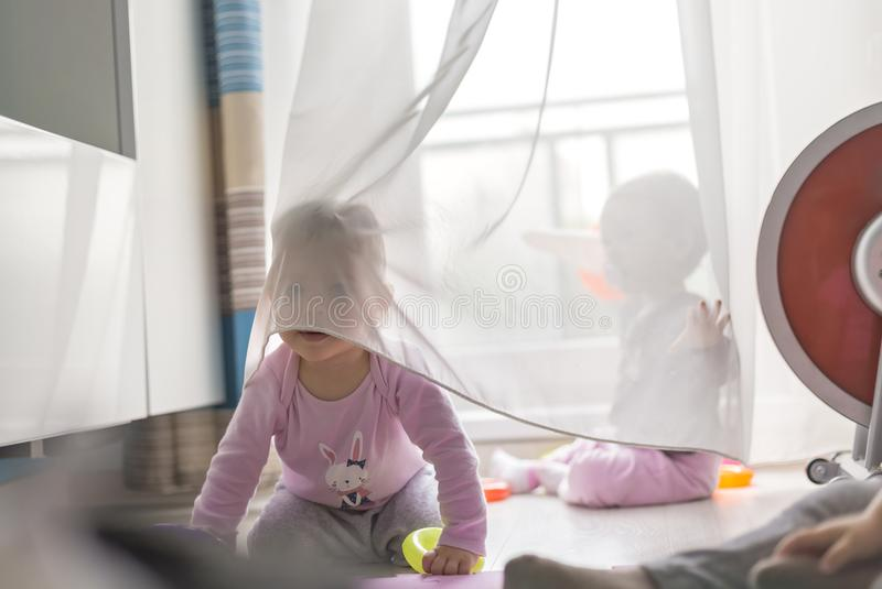Twins play with a curtain stock photo