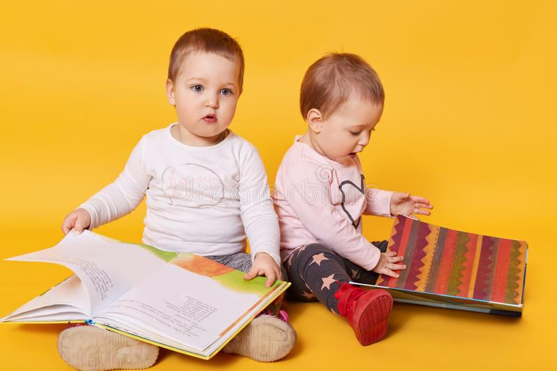 Twins sisters reading books while sitting on floor at home, charming girls playing while their mommy cooking breackfast, girls royalty free stock image