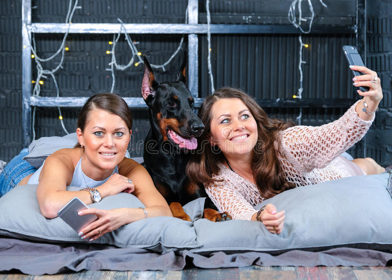 Twins som gör selfie i säng med den stora hunden fotografering för bildbyråer