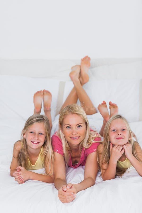 Twins som ligger med deras moder i säng arkivbild