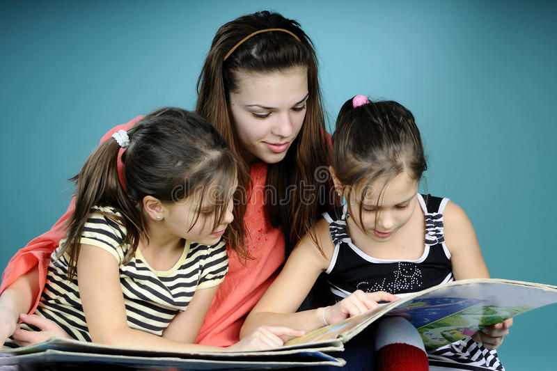 Twins and young educator studying. And reading book royalty free stock image