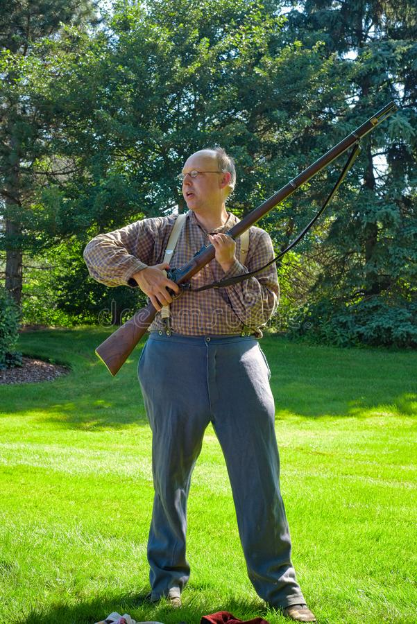 Civil War rifleman demo. TWINSBURG, OH - JUNE 30, 2018: A reenactor demonstrates the use of a Civil War era rifle at an all-day history event at the Twinsburg stock photos