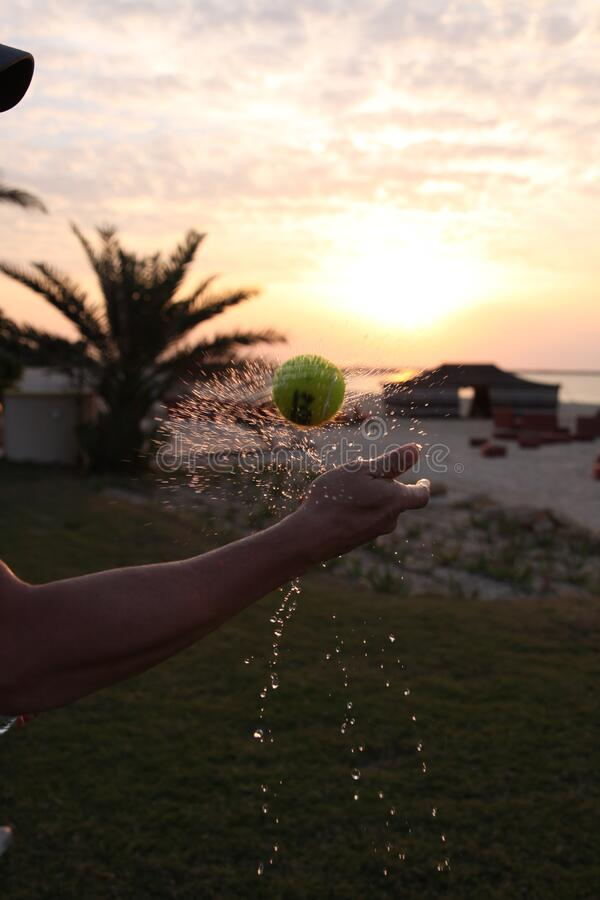 Twist splash of tennis ball on the sunset stock images