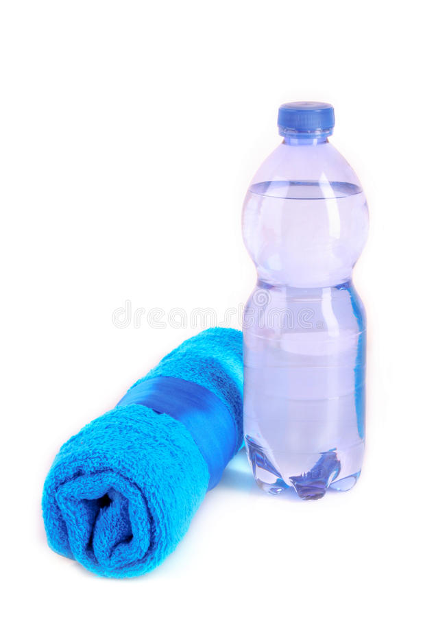 Twisted blue towel and bottle of sparkling water royalty free stock image