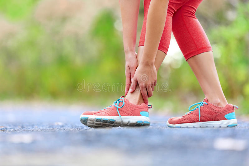 Twisted broken ankle - running sport injury. Female runner touching foot in pain due to sprained ankle royalty free stock photo