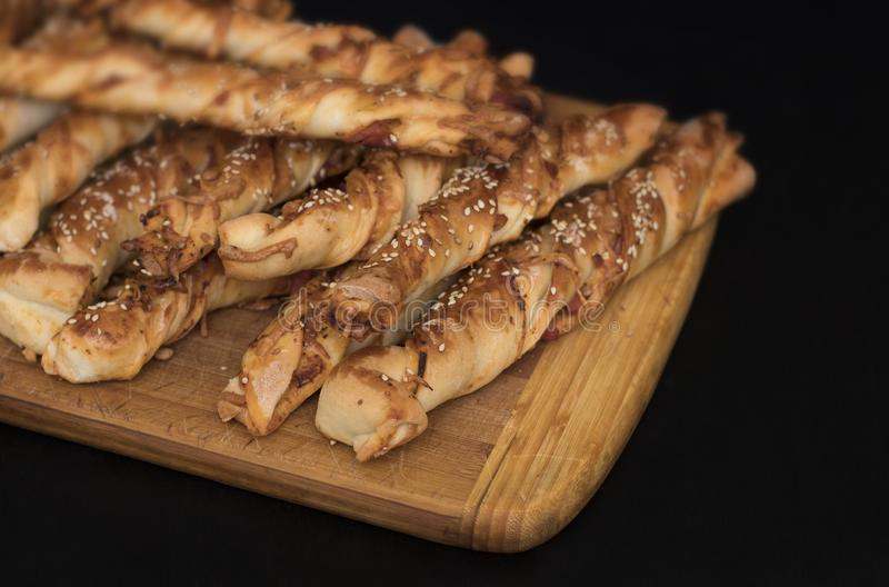 Twisted cheese bread sticks with ham and sesame seeds on a wooden board stock photography