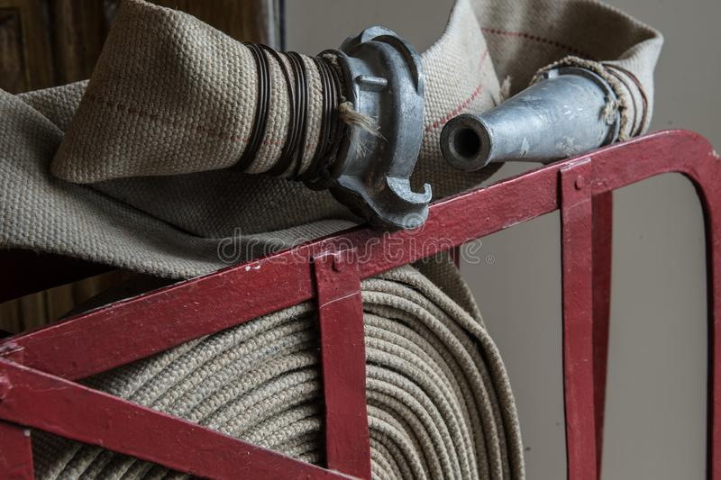 Twisted fire hose on fire shield. An old gray fire hose made of fireproof material attached to a special stand on a wooden wall. Connecting pipes made of metal royalty free stock images