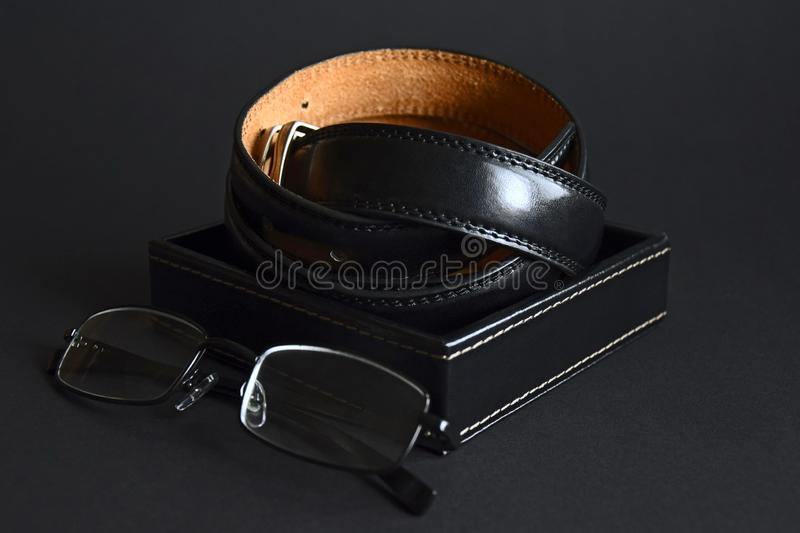 Twisted men`s leather belt in black in a box and eyeglasses on dark background, elegant accessories. Close-up royalty free stock images