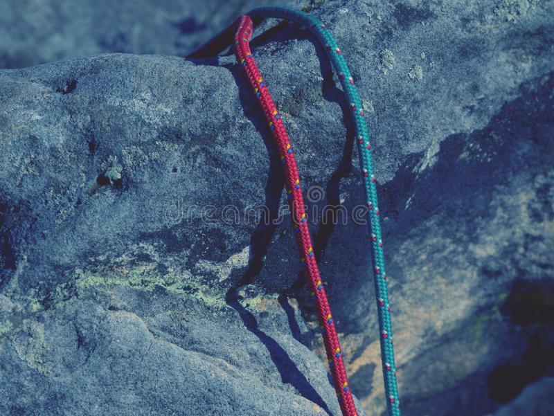 Twisted nylon green and red ropes. Detail of old used rope. On sandstone rock wire weathering weathered wall vertical trekking travel tool thread texture test stock photos