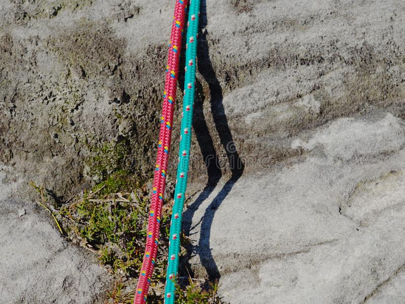 Twisted nylon green and red ropes. Detail of old used rope. On sandstone rock royalty free stock photo