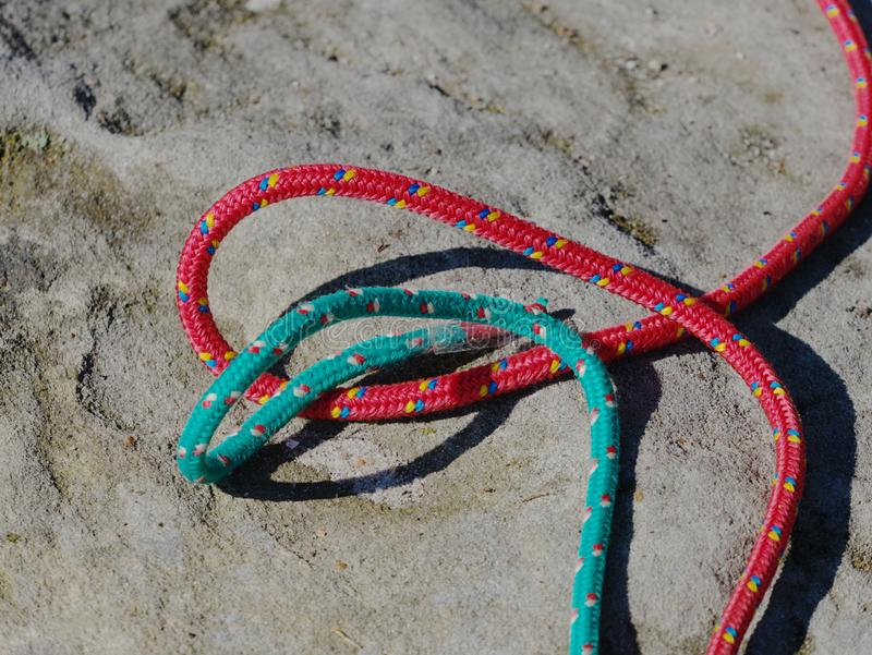 Twisted nylon green and red ropes. Detail of old used rope. On sandstone rock royalty free stock image
