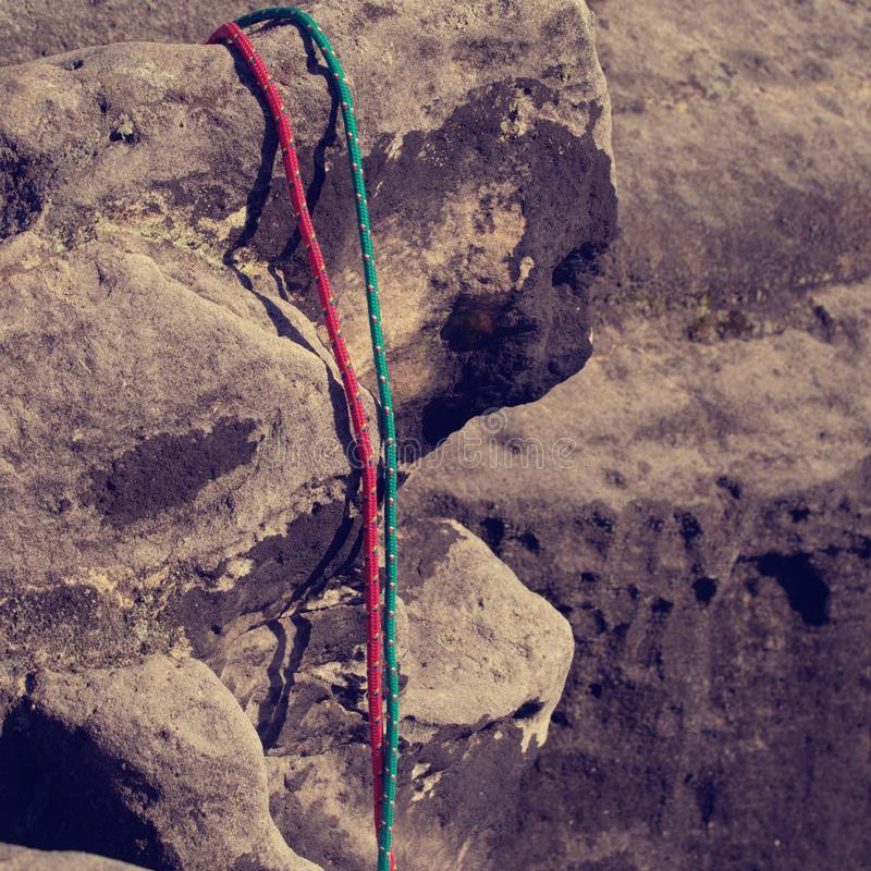 Twisted nylon green and red ropes. Detail of old used rope. On sandstone rock royalty free stock images