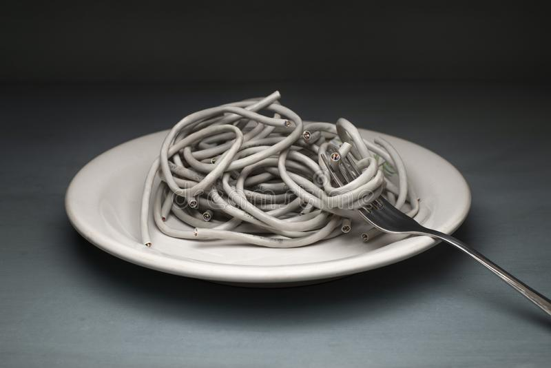 Twisted-pair ADSL in the form of paste wrapped around a fork. Wire on a white plate stock photo