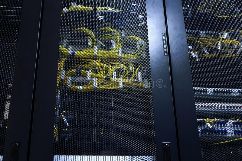 Twisting internet wires and optical cables in server room office racks. Modern data center working, connected and transmitting royalty free stock photo