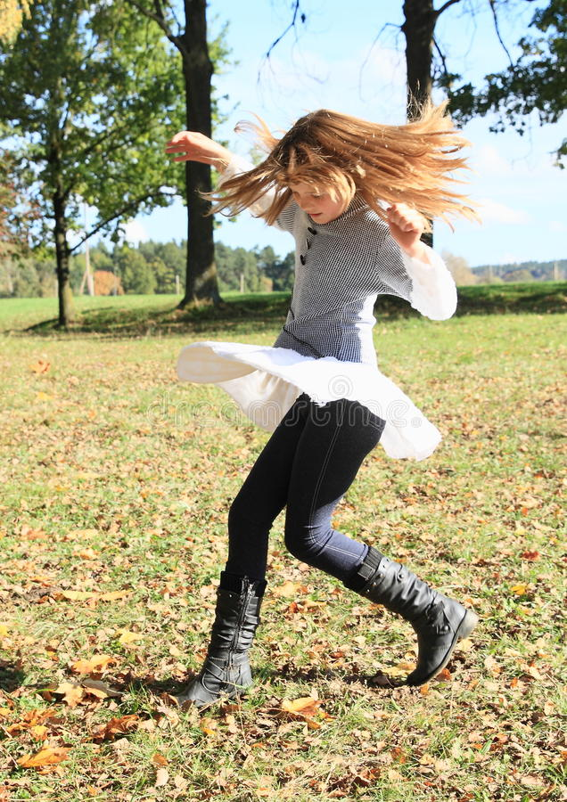 Twisting little girl. Twisting kid - smiling girl with flying hair and white skirt royalty free stock photos