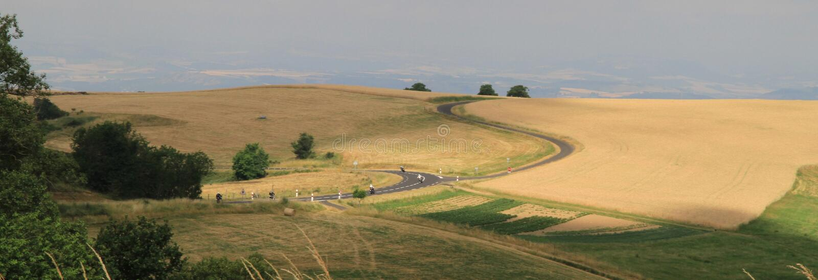 Twisting roads in the Auvergne wheat fields in France. Motorcycles scythe through the landscape with patchwork fields below the high ground of wheat fields and royalty free stock photo