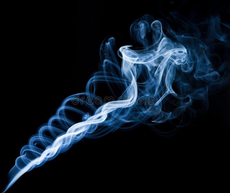 Twisting smoke spiralon black background. Twisting smoke spiral on black background, horizontal shot stock image