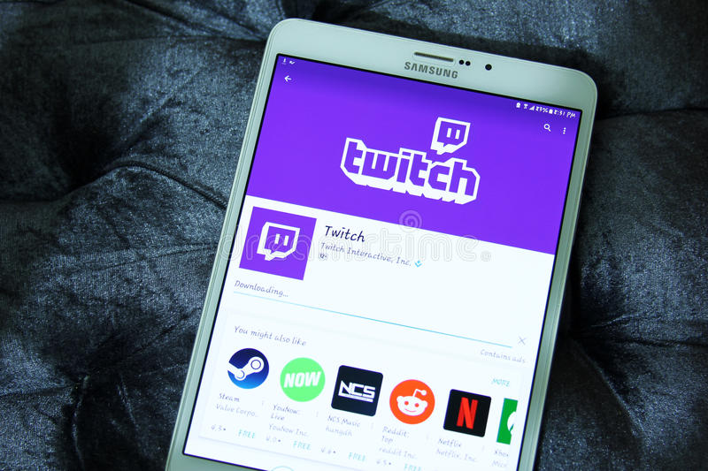 Twitch mobile app. Downloading twitch mobile application from google play store on samsung tablet. twitch is a live streaming video platform for gamers owned by stock photo