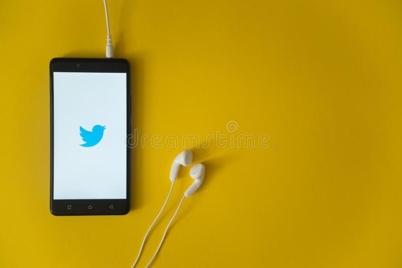 Twitter-embleem op het smartphonescherm op gele achtergrond stock foto