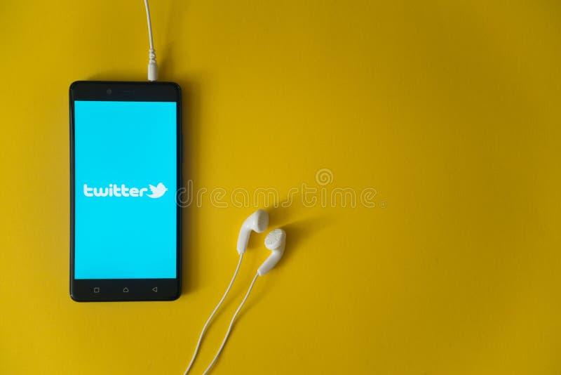 Twitter-embleem op het smartphonescherm op gele achtergrond stock afbeelding