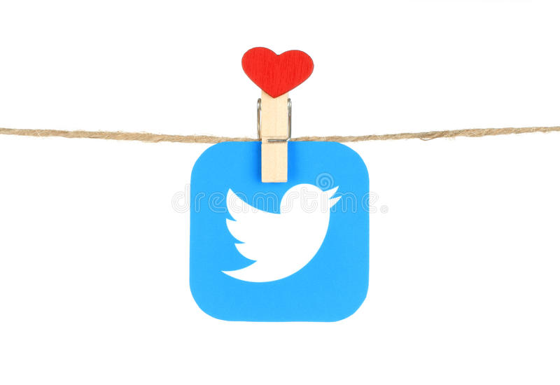 Twitter logo, printed on paper, hangind on a rope with red heart. Kiev, Ukraine - August 02, 2016: Twitter logo, printed on paper, hangind on a rope with red stock photo