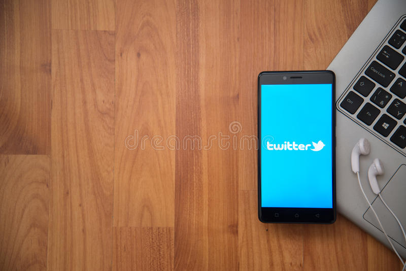 Twitter. Los Angeles, USA, april 16, 2017: Twitter application on smartphone with earphones and notebook on wooden background